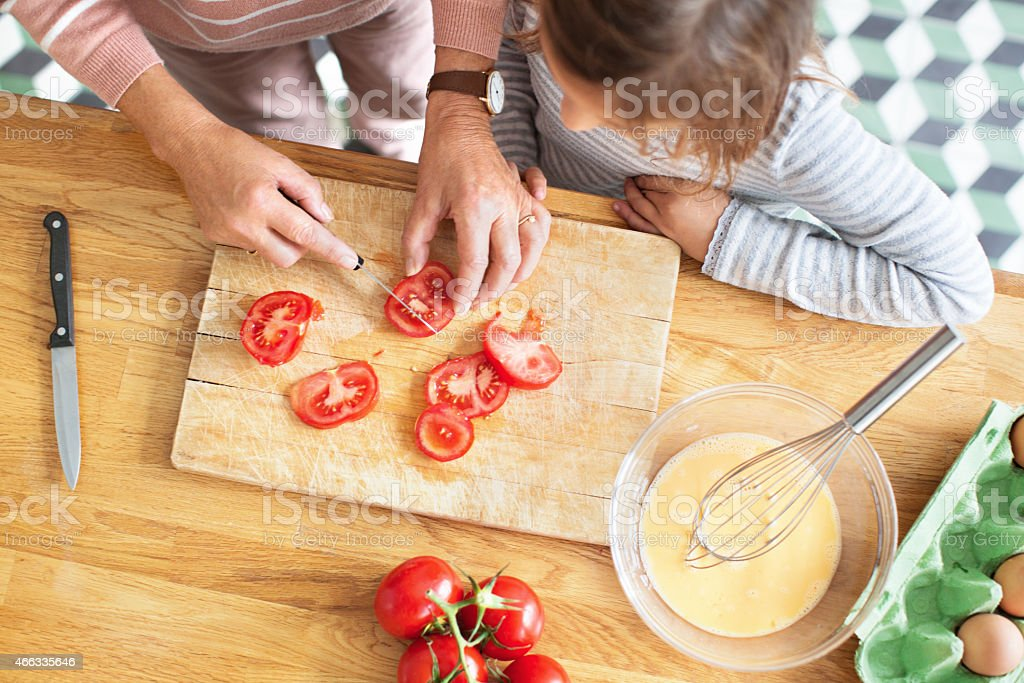 Elderly woman chopping tomatoes with her granddaughter in kitchen stock photo