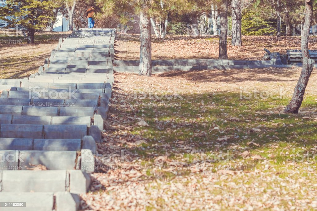 Elderly woman climbing the stairs in the park alone stock photo