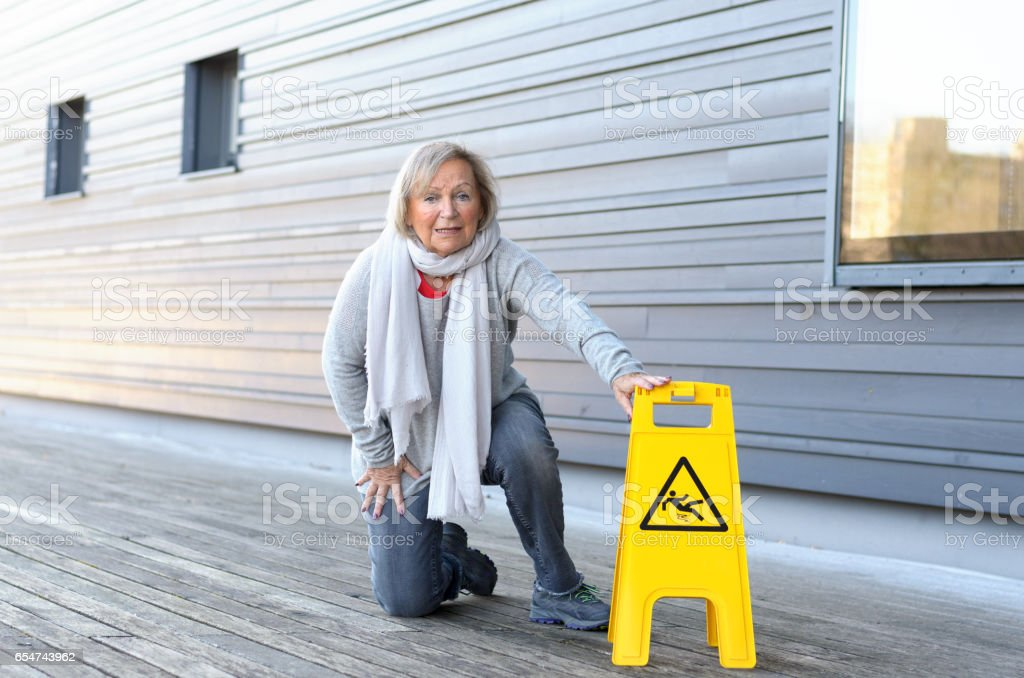 Elderly woman crawling on her knees after slipping stock photo