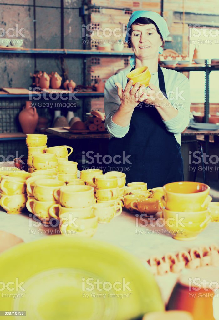 Elderly woman displaying cups stock photo