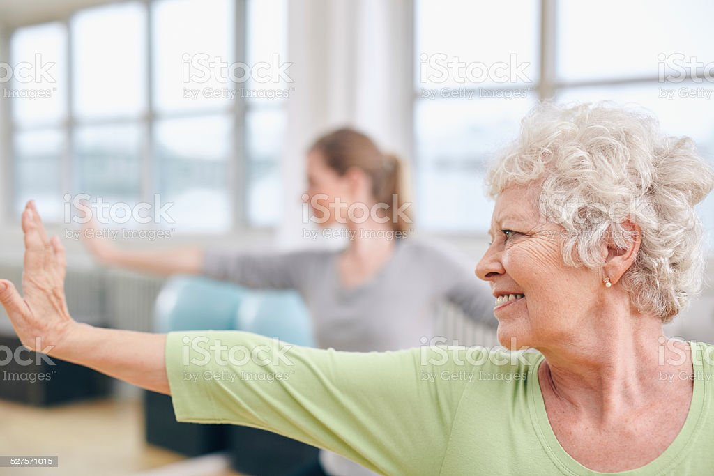 Elderly woman doing stretching workout at yoga class stock photo