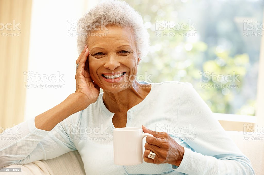 Elderly woman drinking a cup of coffee at home stock photo
