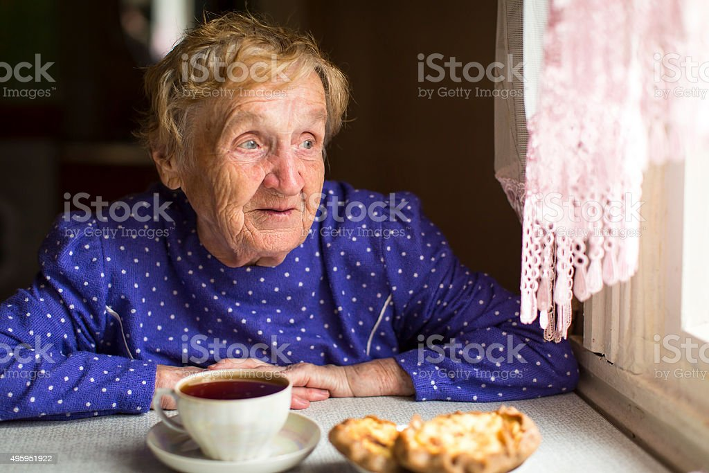Elderly woman drinking tea while sitting at a table stock photo