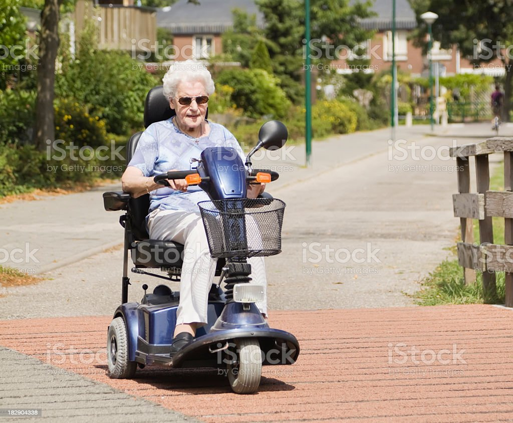 Elderly woman driving mobility scooter down quiet street stock photo