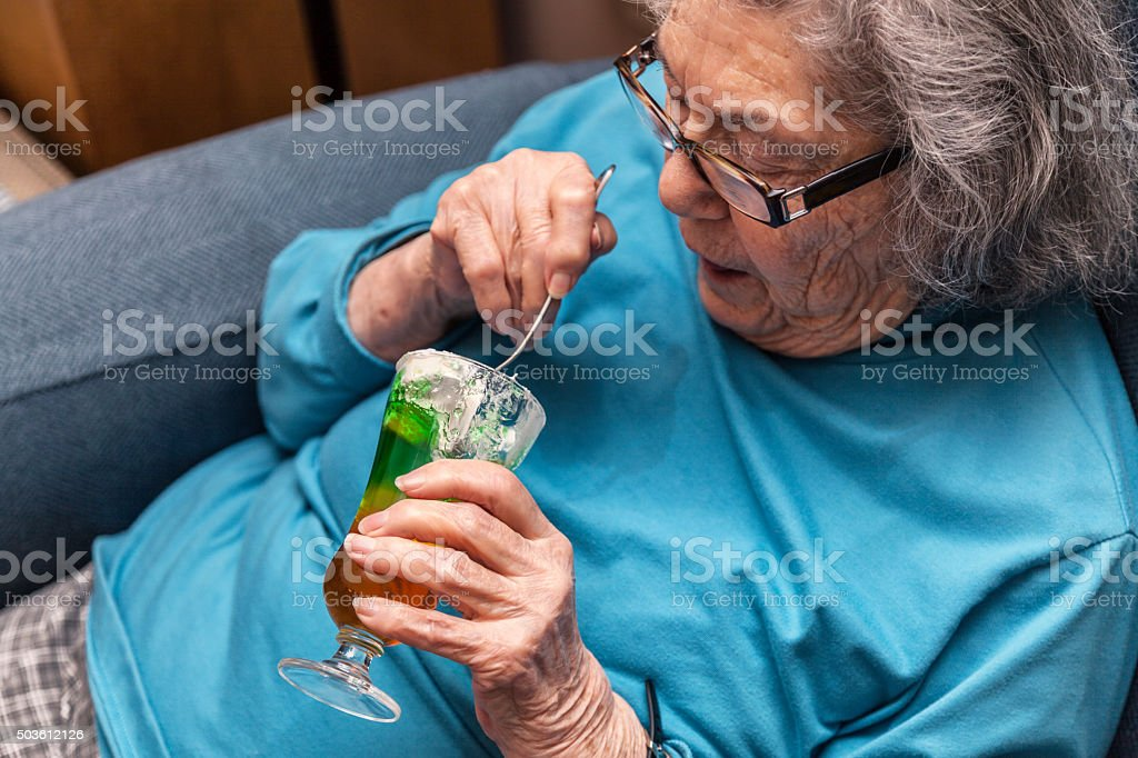 Elderly Woman Eating Parfait Whipped Cream Gelatin Dessert stock photo