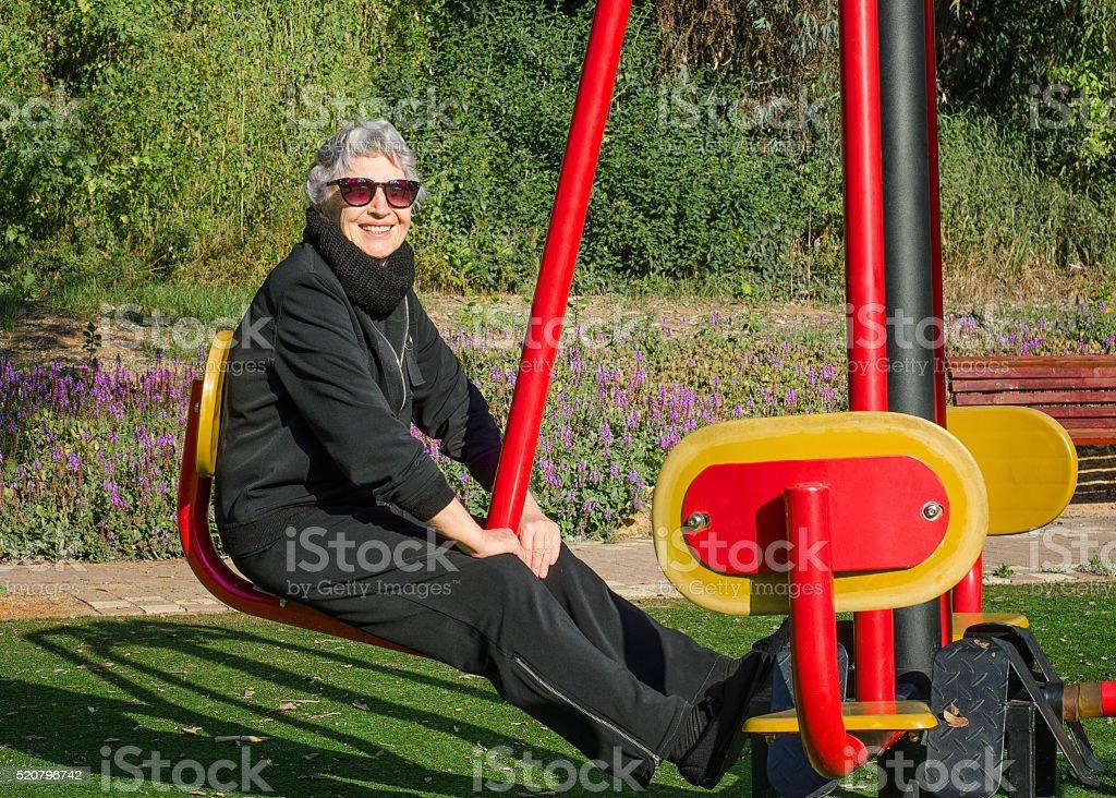Elderly woman enhances flexibility of her waist and legs stock photo