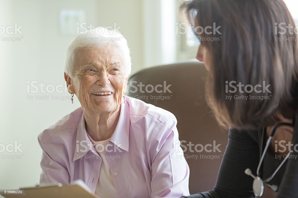 Elderly woman getting care in a home like setting stock photo