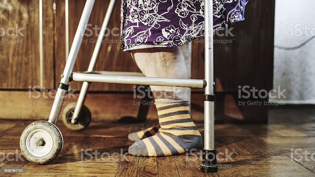 Elderly woman going slowly with the help of walker stock photo