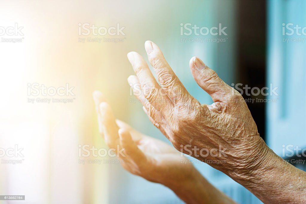 Elderly woman hands praying with peace of mind and faithfully. stock photo