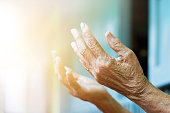 Elderly woman hands praying with peace of mind and faithfully.