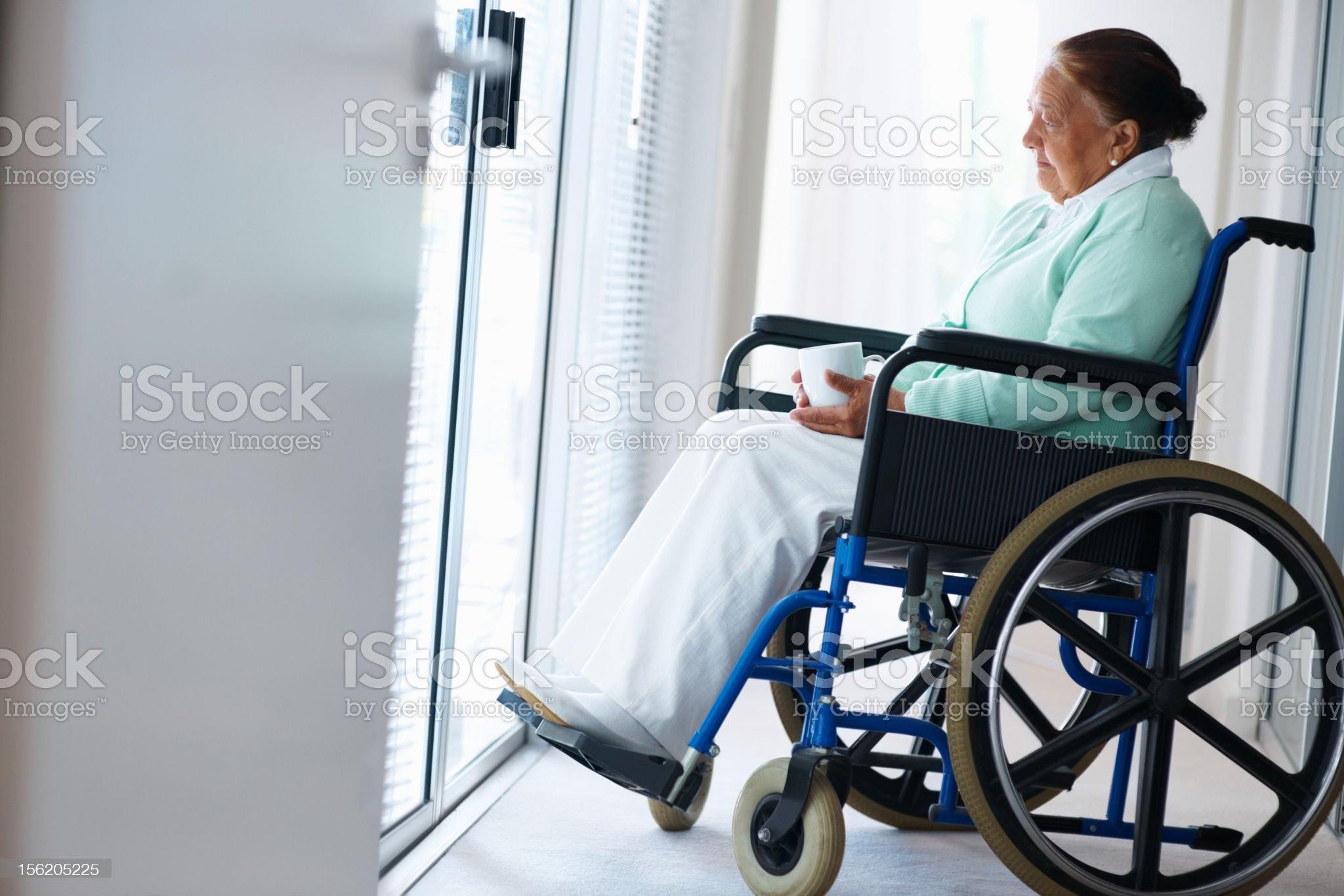 Elderly woman having coffee on a wheelchair royalty-free stock photo