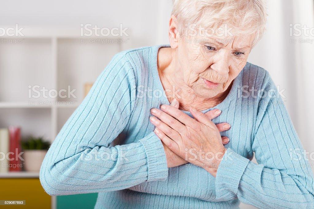 Elderly woman having heart attack stock photo