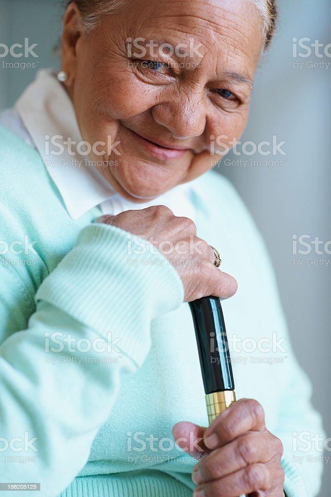 Elderly woman holding a walking stick royalty-free stock photo
