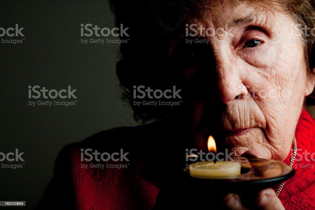 Elderly Woman Holding Candle stock photo