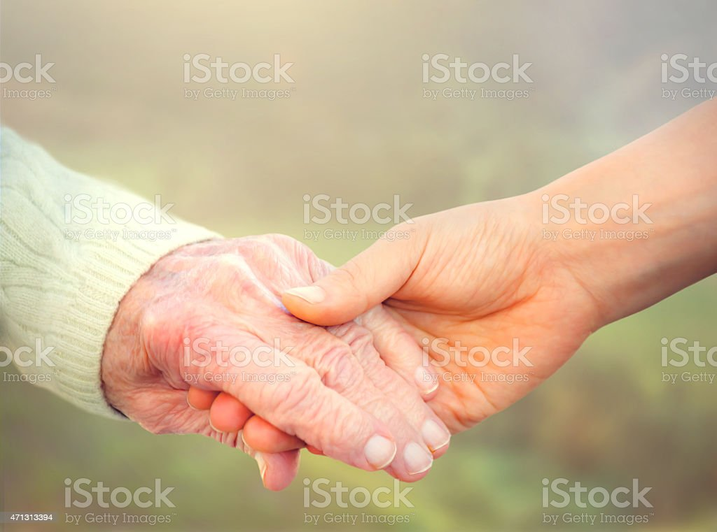 Elderly woman holding hands with young caregiver stock photo