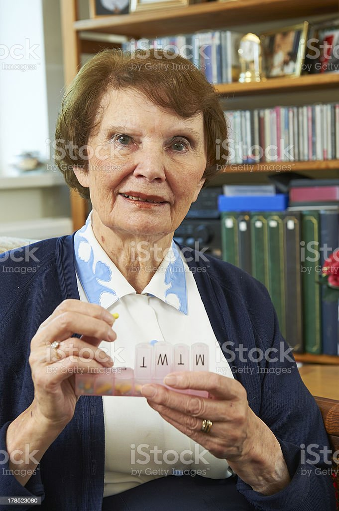 Elderly woman holding her pill box royalty-free stock photo