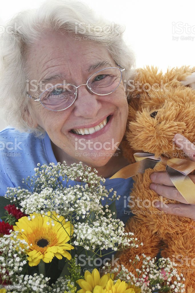 Elderly woman holding teddy bear and flower bouquet stock photo