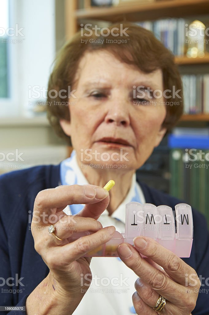 Elderly woman holing medication in front of her royalty-free stock photo