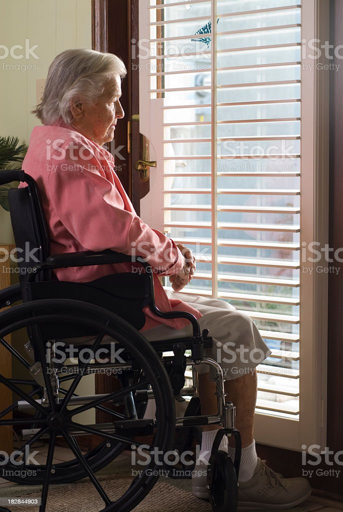 Elderly woman in a wheelchair looking out a window stock photo