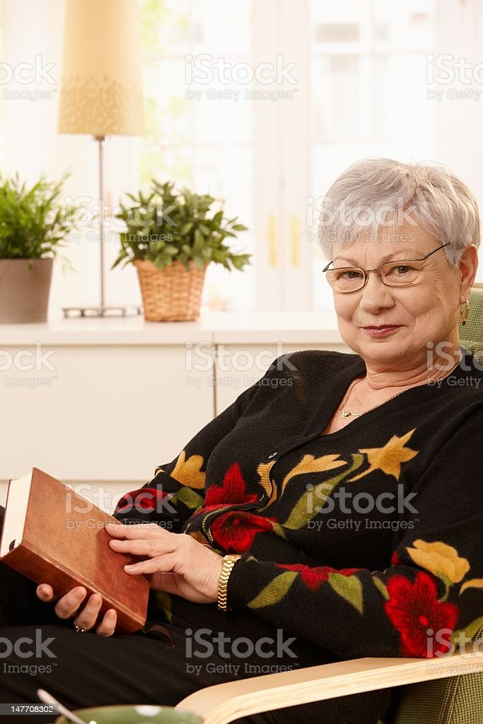 Elderly woman in armchair with book royalty-free stock photo
