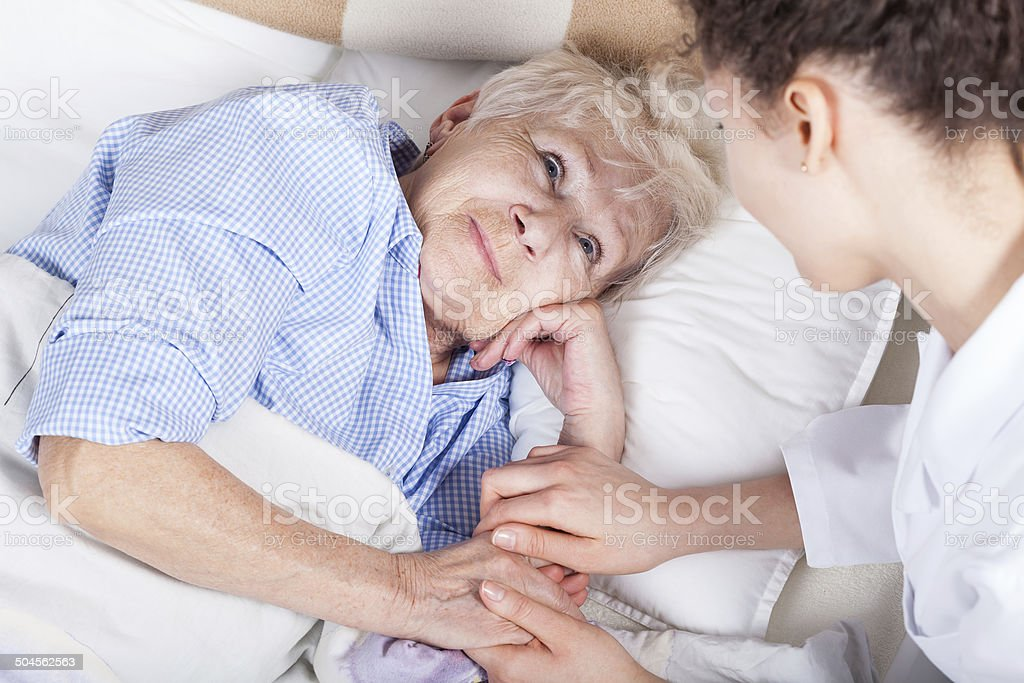 Elderly woman in bed stock photo