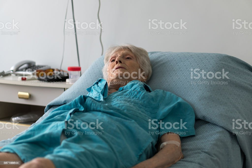 Elderly woman in hospice bed. Selective focus stock photo