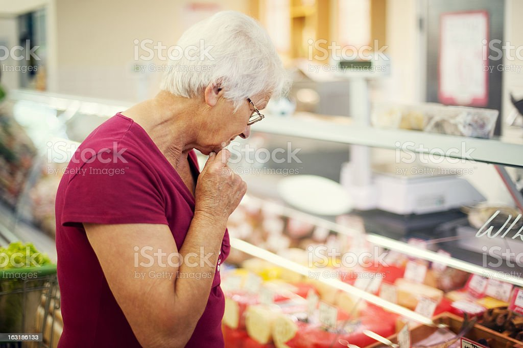 Elderly woman in red shirt examining cheeses at a market royalty-free stock photo