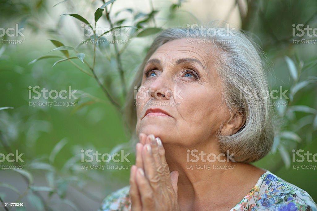 elderly woman in  summer park stock photo