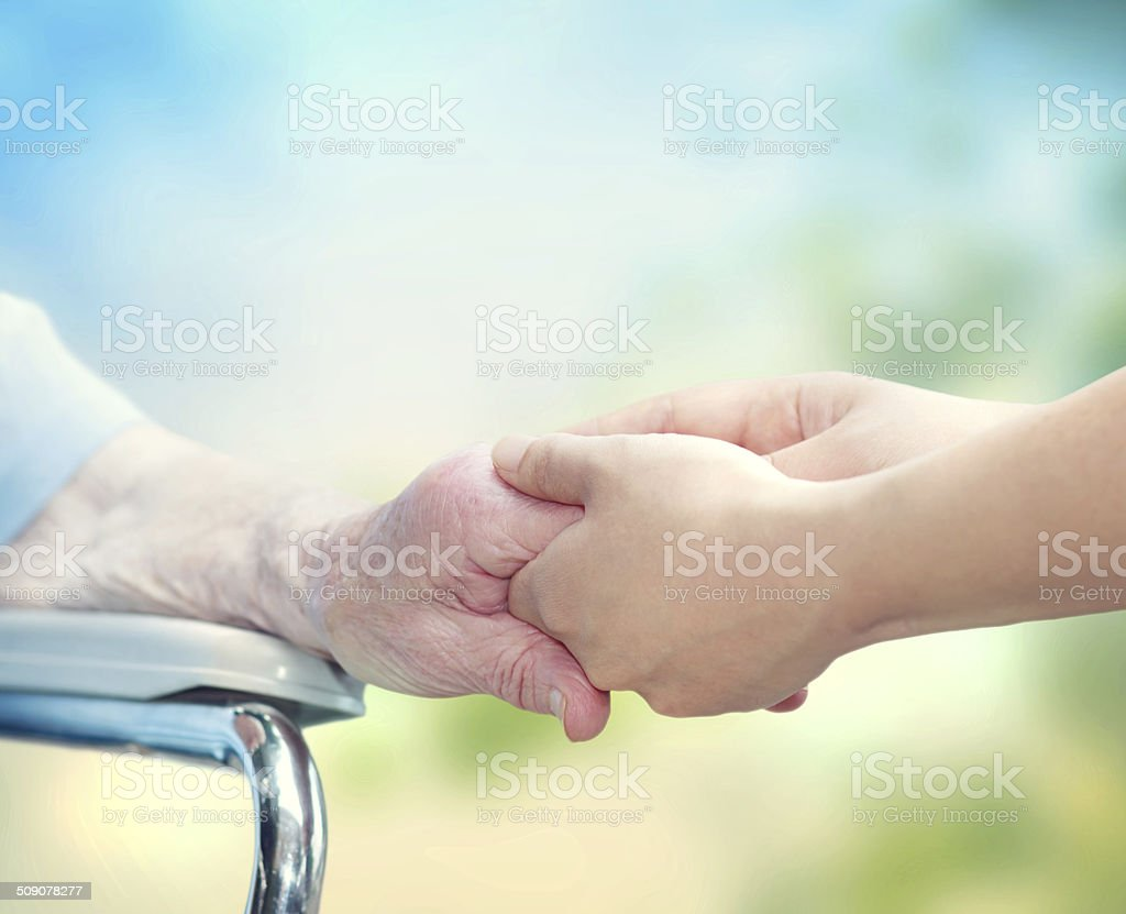 Elderly woman in wheel chair holding hands with young caretaker stock photo