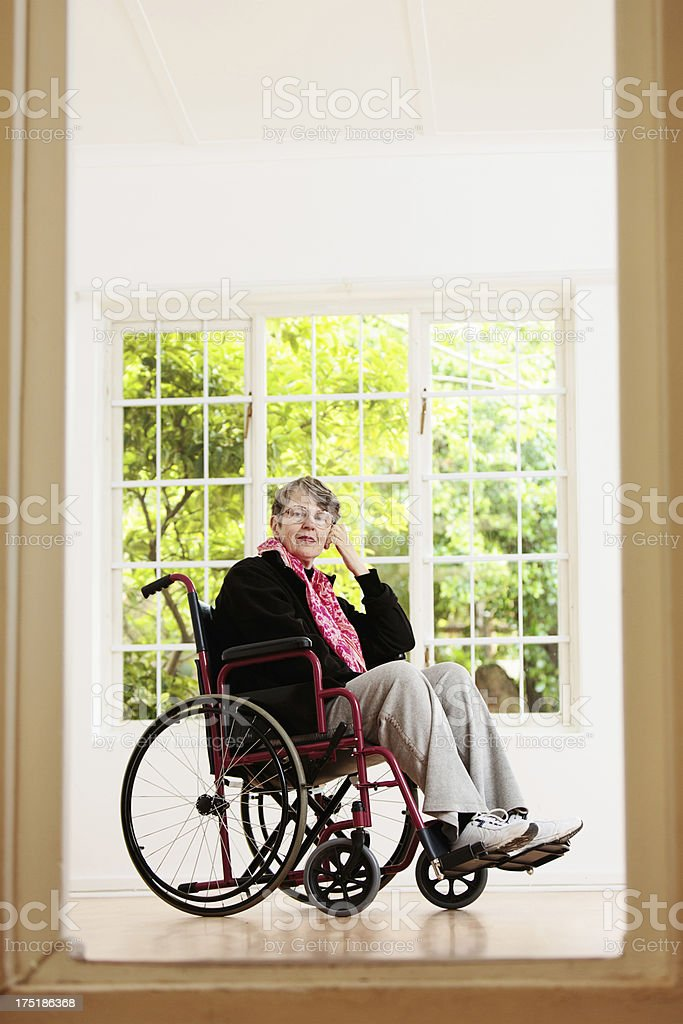 Elderly woman in wheelchair considers her situation, head on hand stock photo