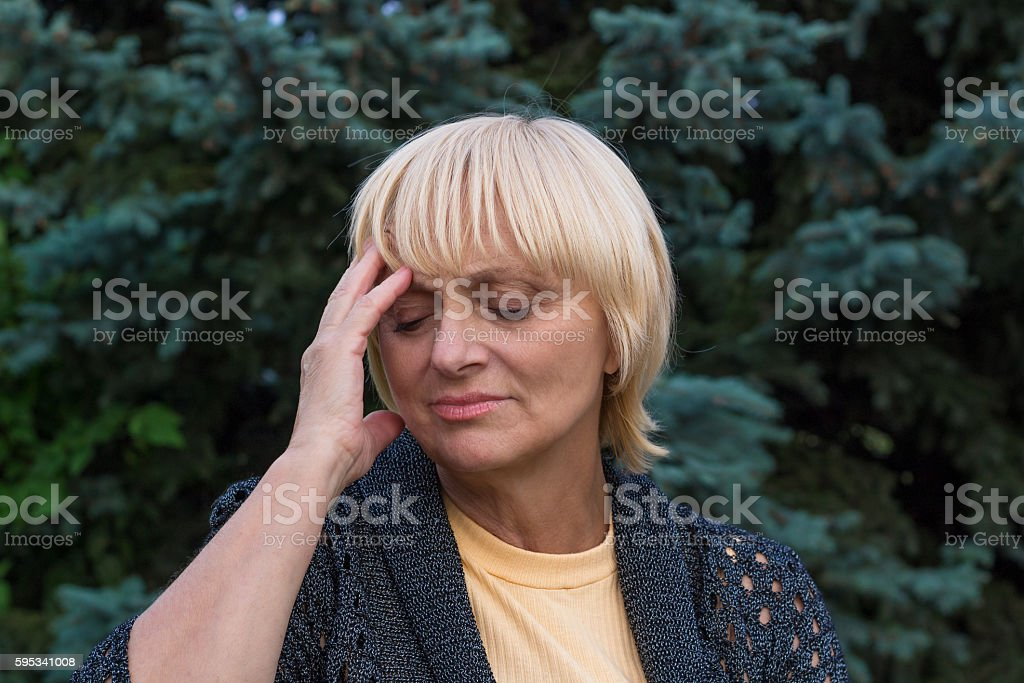 Elderly woman is having a headache and touching her head stock photo