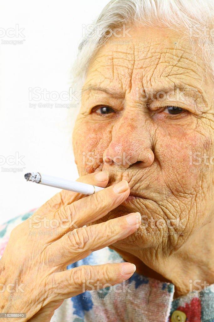 Elderly woman is smoking stock photo