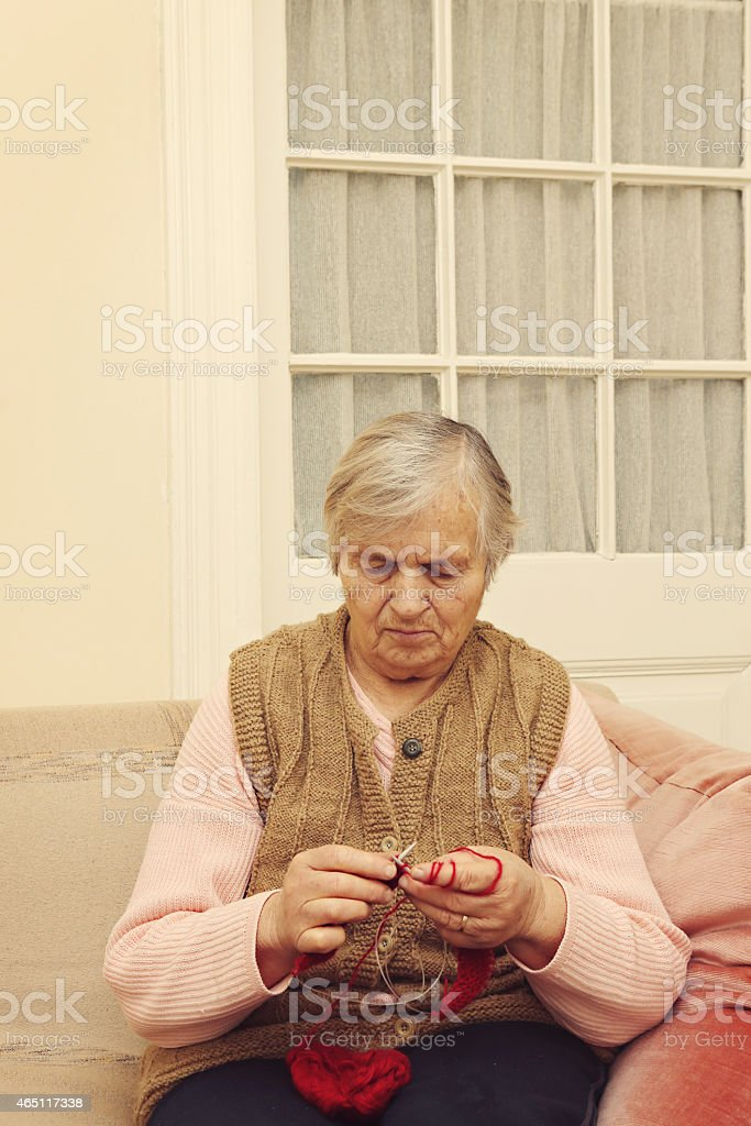 Elderly woman knitting with red wool stock photo