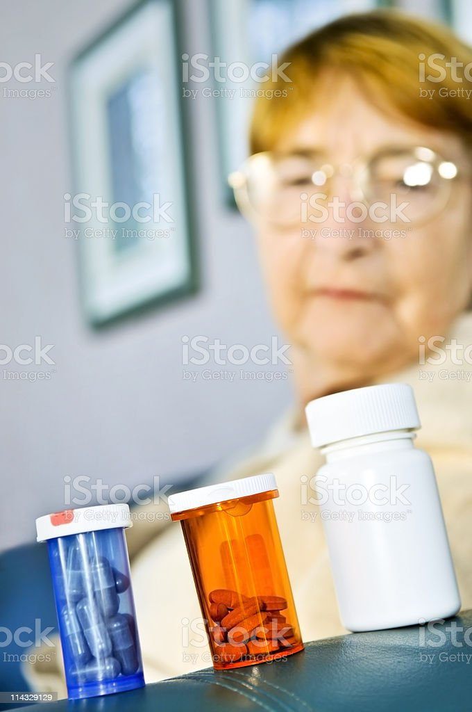 Elderly woman looking at pill bottles royalty-free stock photo