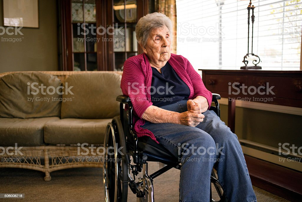 Elderly Woman Looking Out a Window in a Nursing Home stock photo