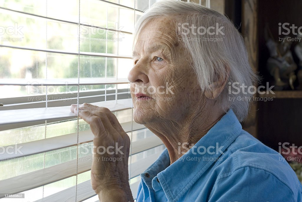 Elderly woman looking out a window. stock photo