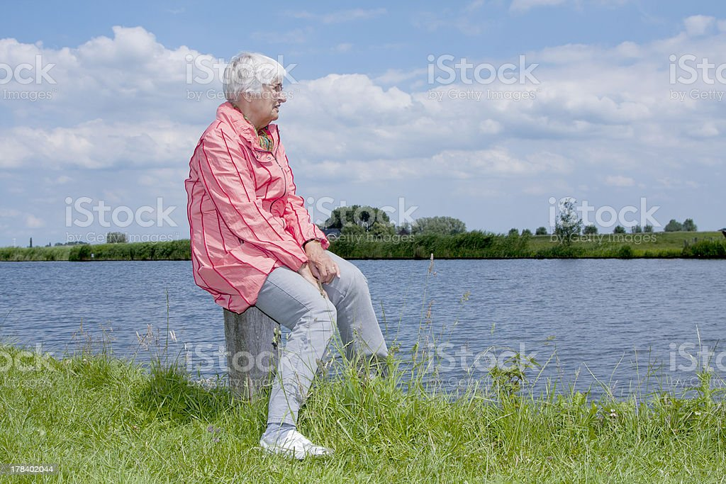 Elderly woman looking out over river Eem (the Netherlands) stock photo