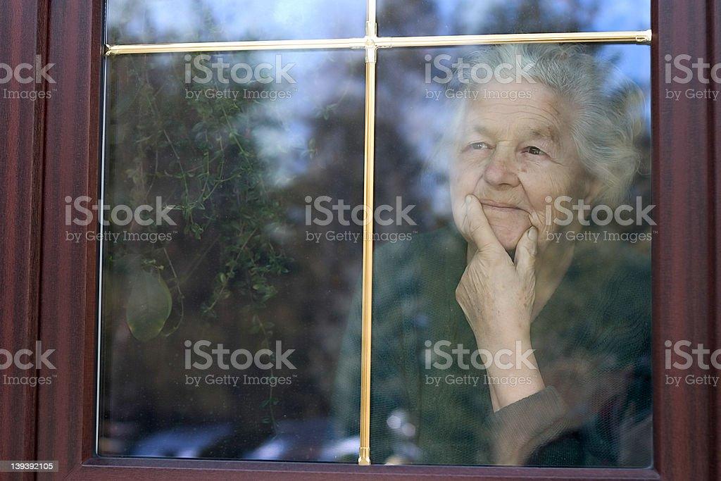 elderly woman looking through the window royalty-free stock photo