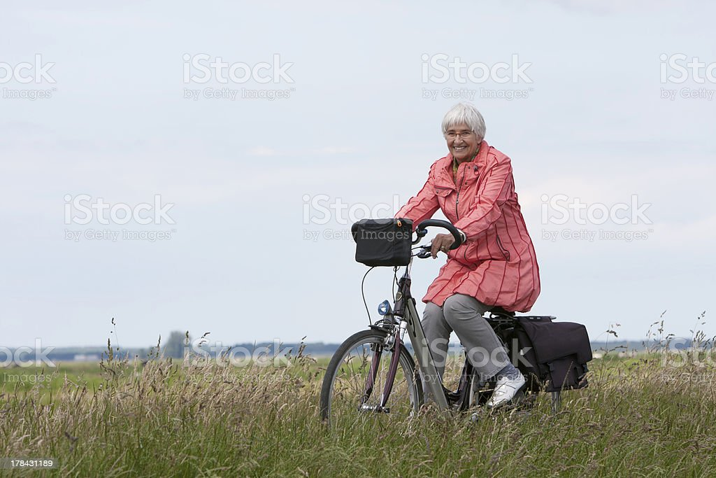 Elderly woman on a bicycle in Dutch polder stock photo