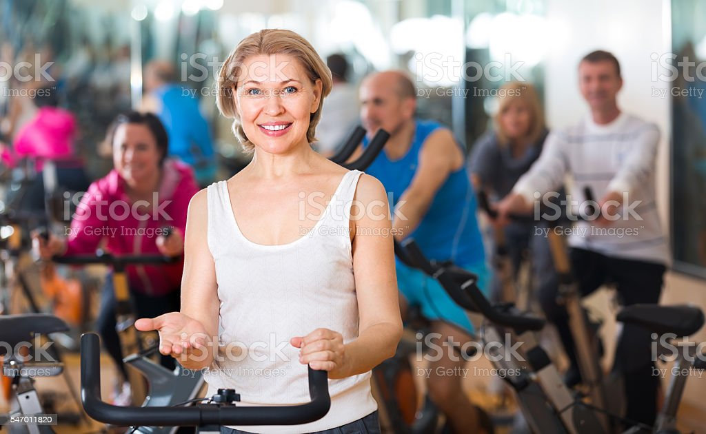 Elderly woman on fitness cycle in a gym stock photo