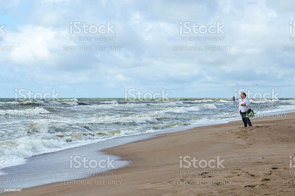 Elderly woman on shore of restless Baltic Sea photographs landscape stock photo
