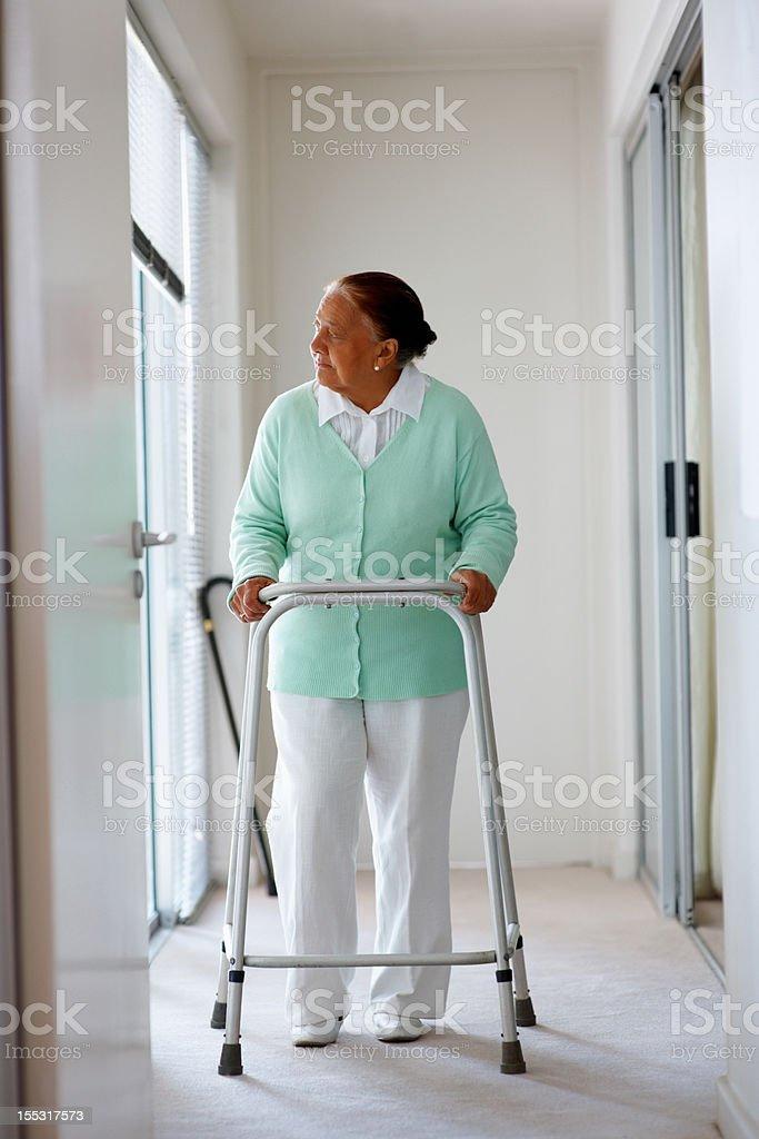 Elderly woman on walker at a hallway royalty-free stock photo