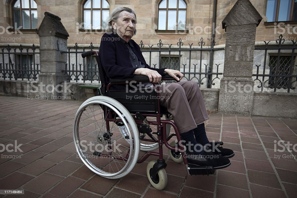 Elderly Woman on Wheelchair in Front of an Old Building stock photo