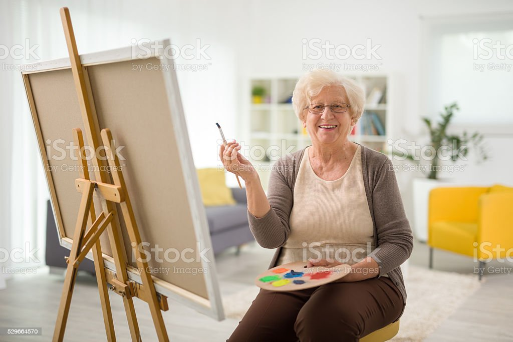 Elderly woman painting on a canvas stock photo