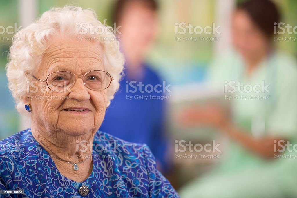 Elderly woman patient foreground. Nurse, daughter. Nursing home. stock photo