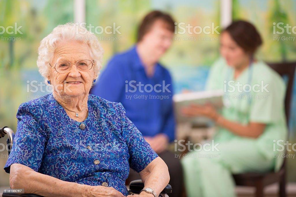 Elderly woman patient foreground. Nurse, daughter. Nursing home. stock photo