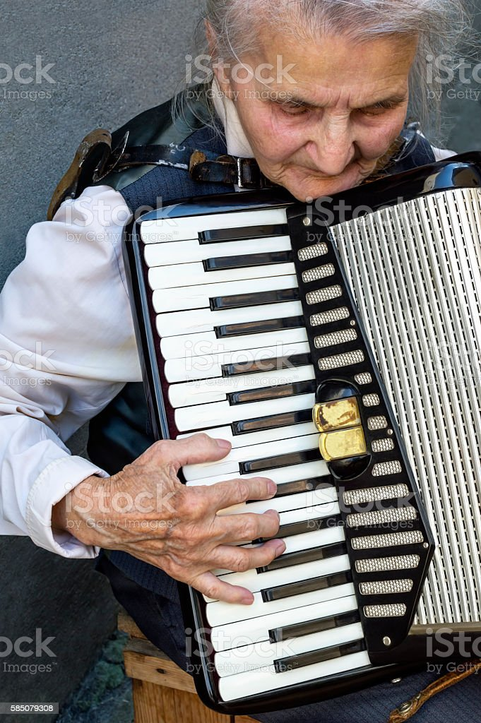Elderly woman playing accordion. stock photo