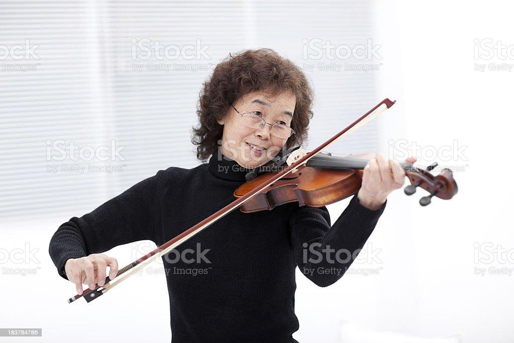 Elderly woman playing violin stock photo