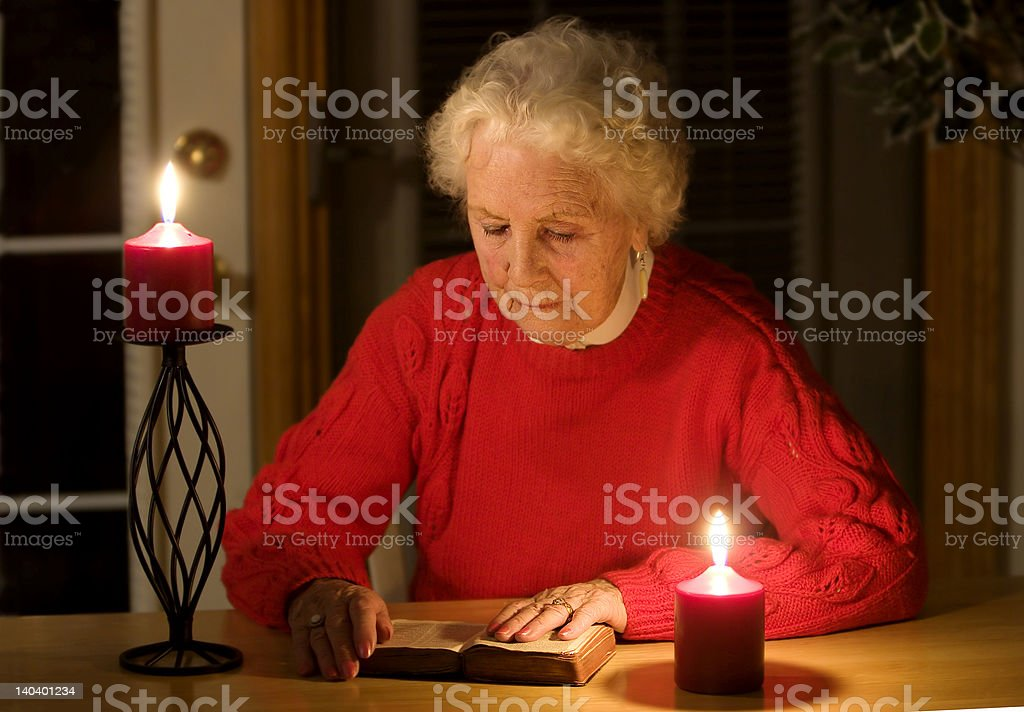 Elderly woman reading during a power outage stock photo