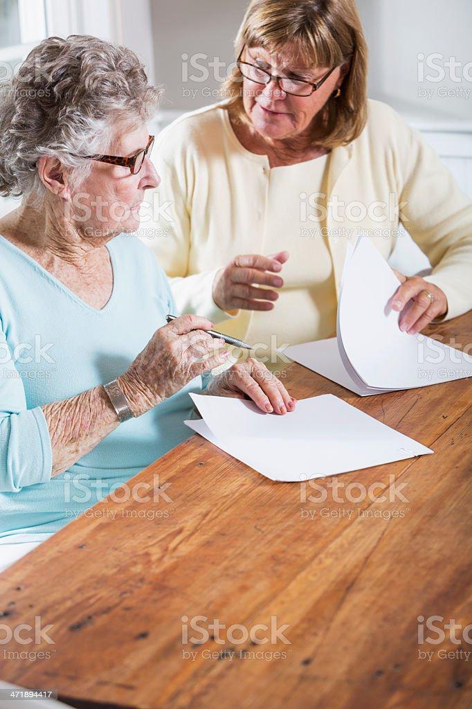 Elderly woman reading paperwork stock photo